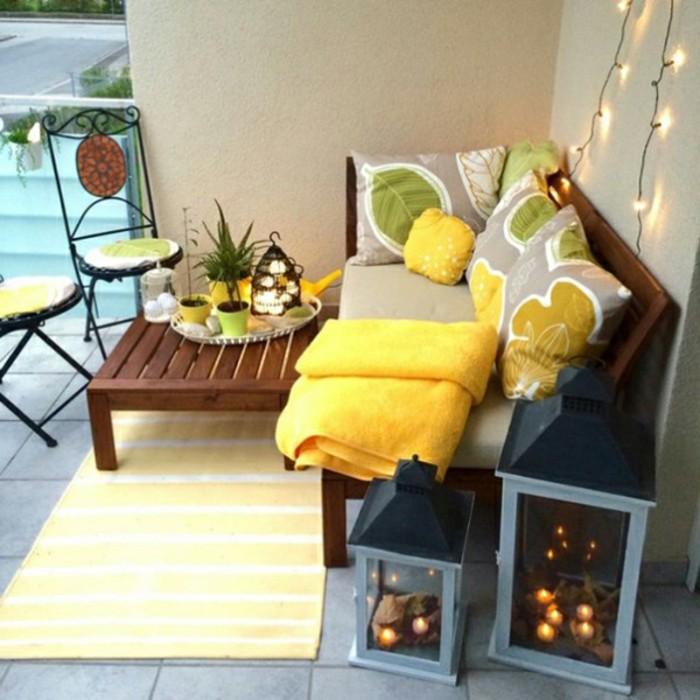 balkongestaltung-mediterran-holzbank-holztisch-massiv-gelber-teppich-bodenfliesen-kissen-pflanzenmotive-metallstühle-kerzen