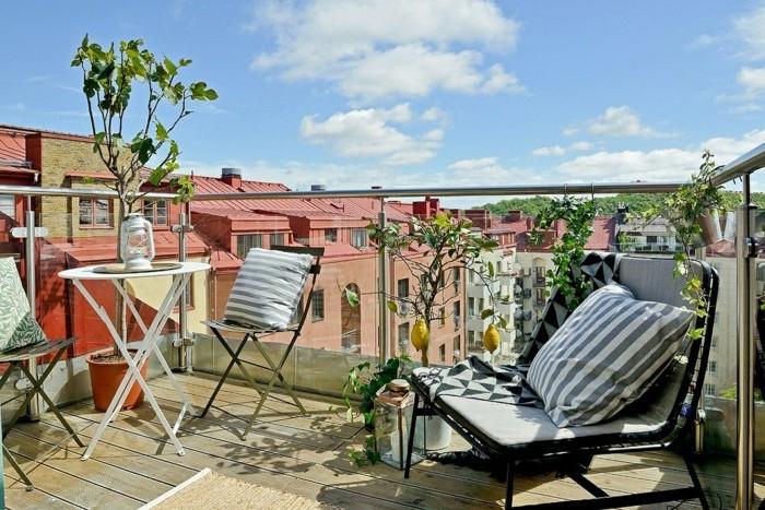 balkongestaltung-mediterran-holzboden-metallstühle-kissen-glasgeländer-weißer-rundtisch-zitronenbaum