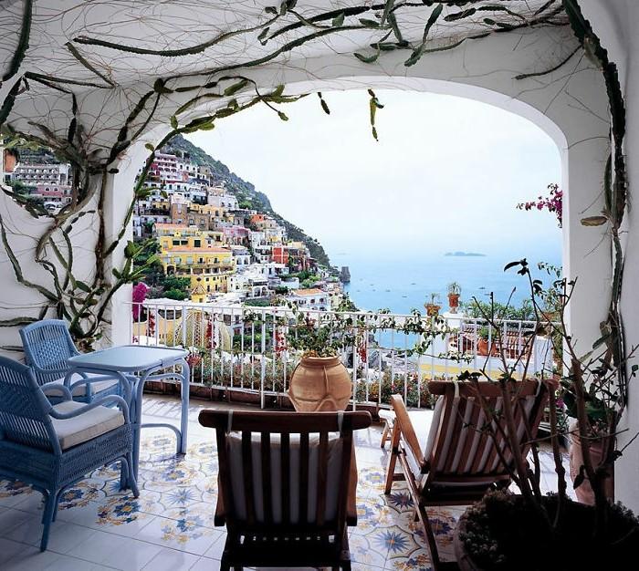 balkongestaltung-mediterran-insel-holzstühle-kissen-blauer-stuhl-weiße-kisse-blauer-tisch-mosaikfliesen