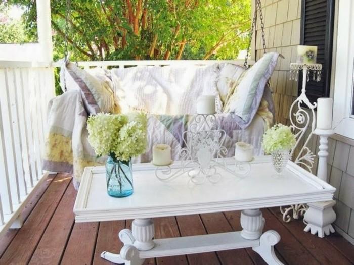 balkongestaltung-schaukel-weiße-schlafdecke-weiße-kissen-weißer-tisch-blumen-vasen-kerzen-holzboden