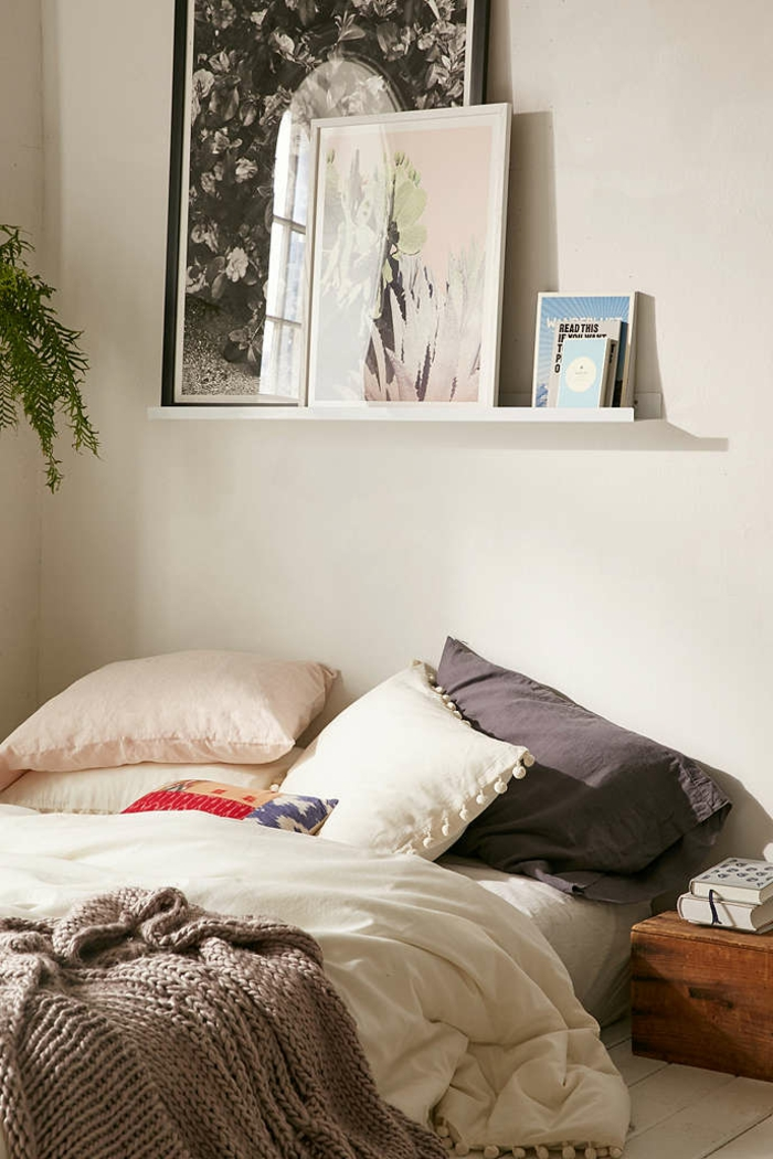 Leiste für Bilderrahmen - große Ölbilder und kleine Bücher, unordentliches Bett gelbe Wände