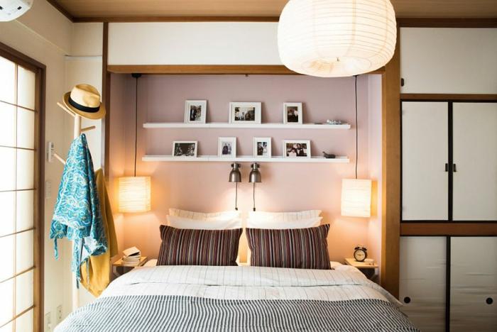Bett mit zwei Leiste, gestreifte Kissen und Bettdecke, zwei Lampen, Baumgarderobe