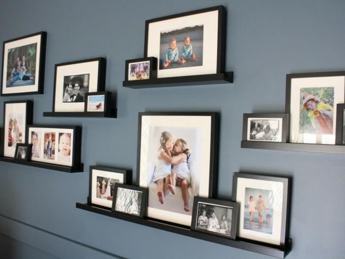 Bilderrahmen in verschiedenen Größe auf schwarzen Bilderboard ordnen, graue Wand