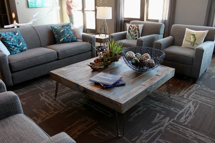 couchtisch-industrial-massivholz-metallbeine-musterteppich-graue-sessel-graue-couch-kisse-musterbezug