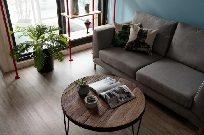 couchtisch-industrial-rund-holz-metallbeine-graue-couch-laminatboden-regal-rot-pflanze