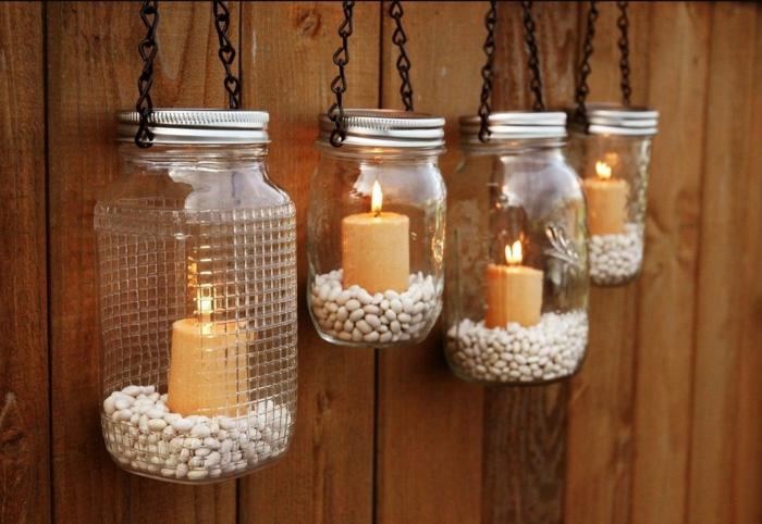 an dem Zaun dekorierte Weckgläser hängen mit Bohnen gefüllt und Kerze drinnen