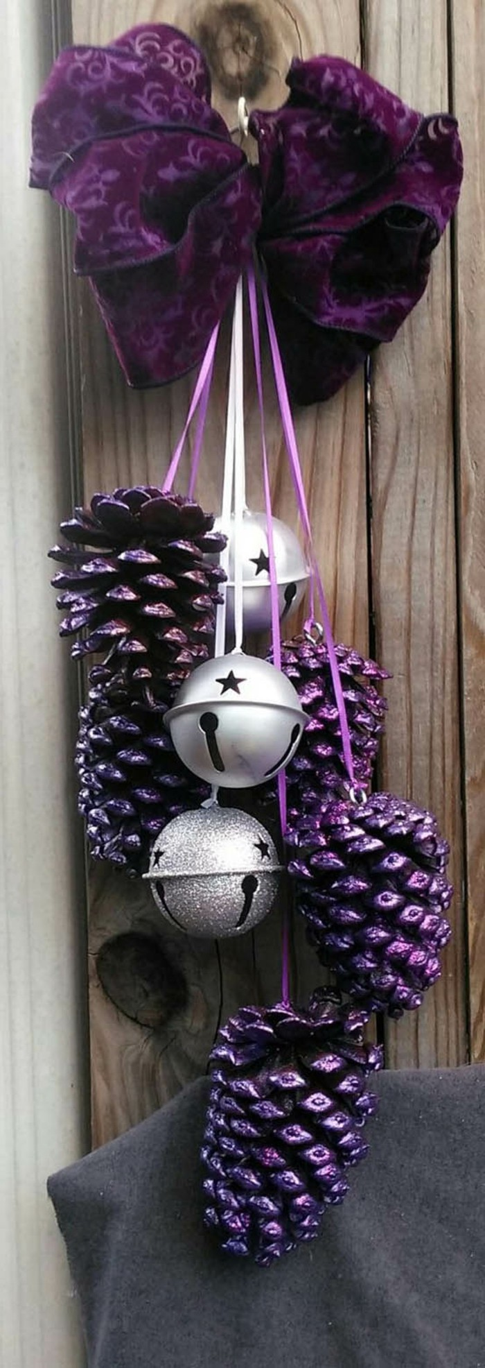 deko-mit-tannenzapfen-lila-gestrichen-lila-band-silberne-glocken