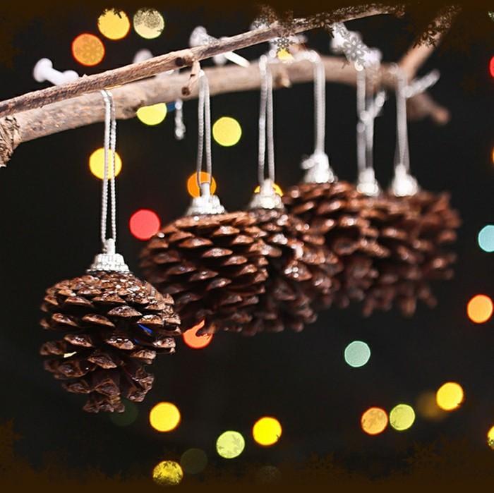 deko-mit-tannenzapfen-von-einem-zweig-hängend-lichte-im-hintergrund