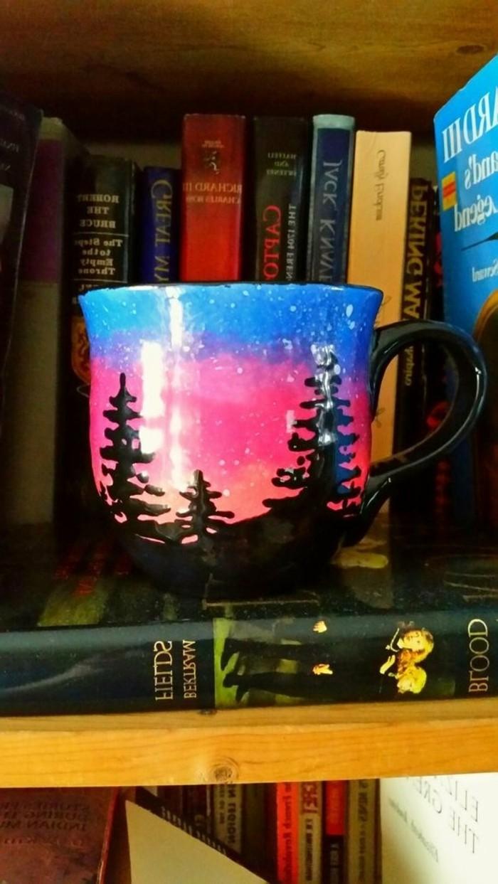 diy-tasse-bemalte-tasse-auf-bücherregal-mit-nordlichem-motiv-sonnenuntergang-blau-und-rosa