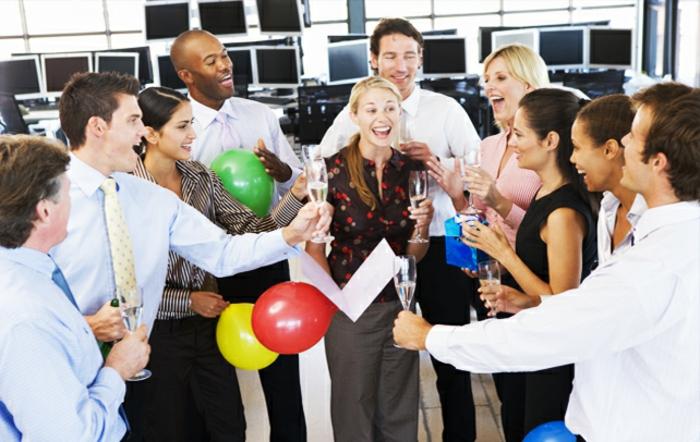 dresscode festlich elegant im büro mit den kollegen feiern ballons und lächelnd champagner