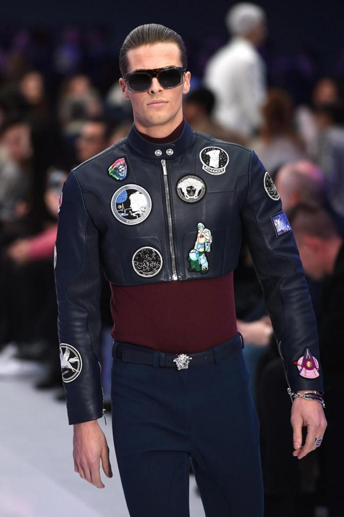 versace lederjacke mit ausgefallenen stempeln brille bluse in farbe bordeaux dunkelblaue hose gürtel