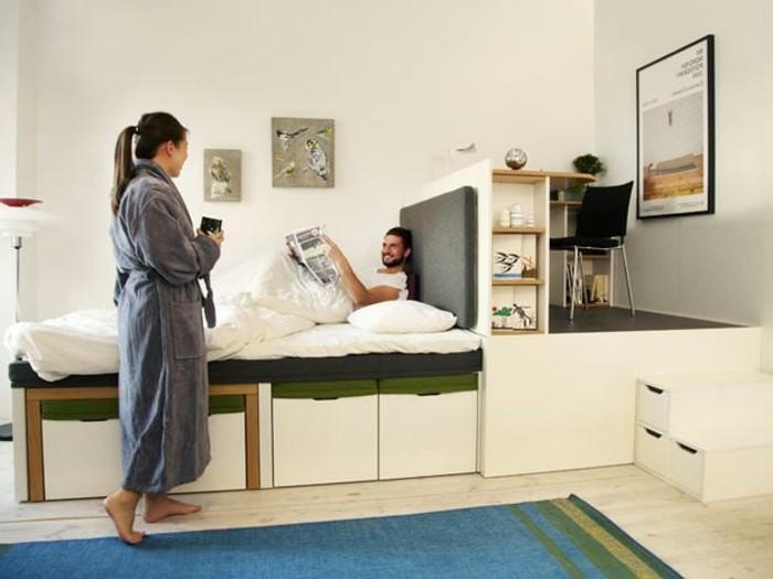 einzimmerwohnung-einrichten-doppelbett-blauer-musterteppich-schreibtisch-regale-treppen-laminat