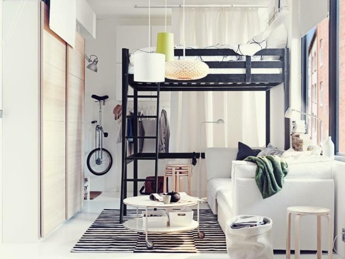 einzimmerwohnung-einrichten-wohnzimmer-hochbett-musterteppich-weiße-couch-weißer-rundtisch-holzhocker-kleiderschrank