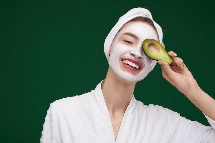 feuchtigkeitsmaske peel off maske selber machen anti pickel maske gesicht selber machen frau mit weißer maske hält avocado im hand