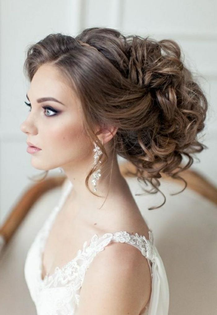 braut mit prachtvoller hochsteckfrisur, weißem kleid und langen ohrringen