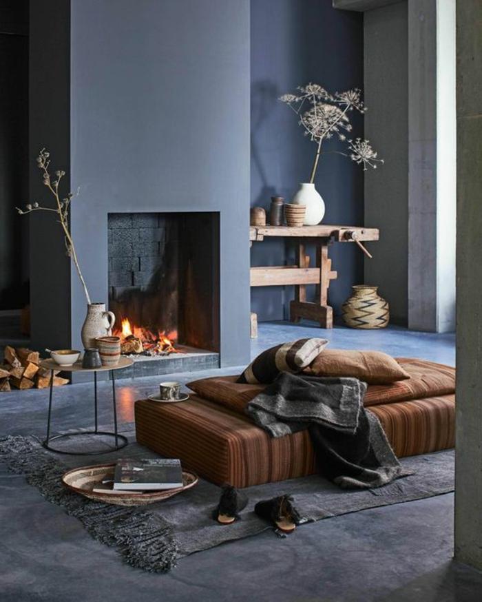 gemauerter-kamin-ikebana-vasen-runder-couchtisch-grauer-teppich-gestreifte-matratze-gestreifte-kissen