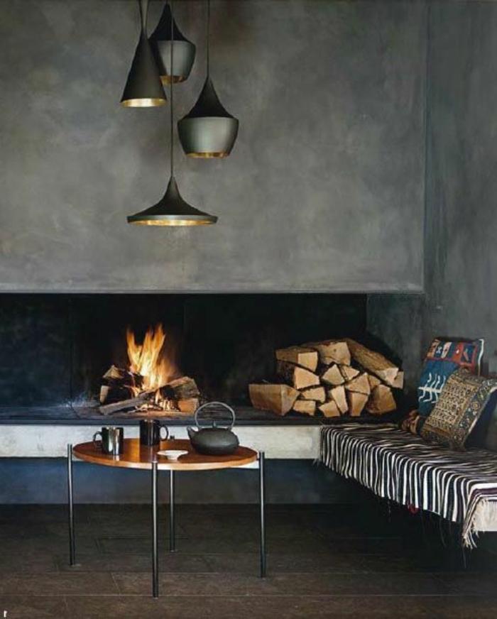 gemauerter-kamin-moderne-beleuchtungskörper-runder-holztisch-metallbeine-couch-gestreifte-decke