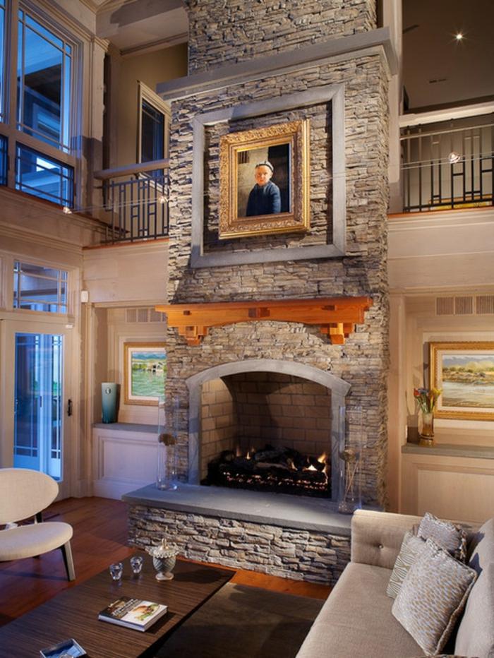 gemauerter-kamin-wohnzimmer-steinwand-laminat-bilder-couch-beige-kissen-grau-holztisch-weißer-stuhl
