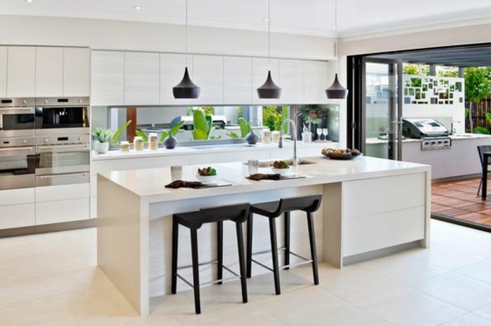 stilvolle küche in weiß mit glasrückwand mit grünen pflanzen