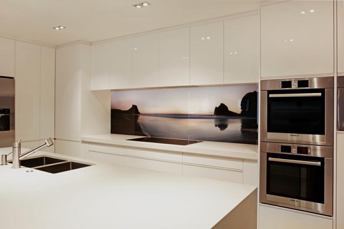 weiße küche mit großer kücheninsel und interessanter küchenrückwand