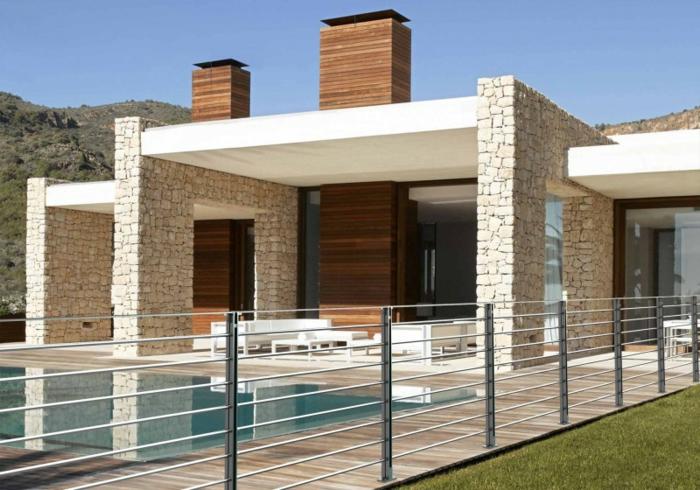 ein modernes Haus mit Schwimmbad und Gartenzaun aus Metall