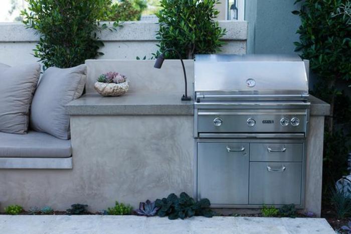 gemauerte Sommerküche mit Grill, graue Gartencouch mit großen Kissen