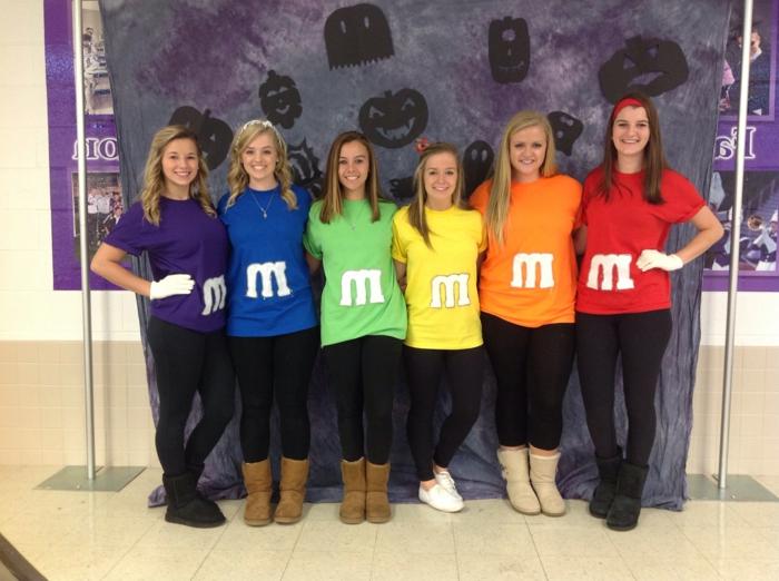 sechs süße Mädchen präsentieren alle Farben von M M Bonbons - Kostüm Gruppe