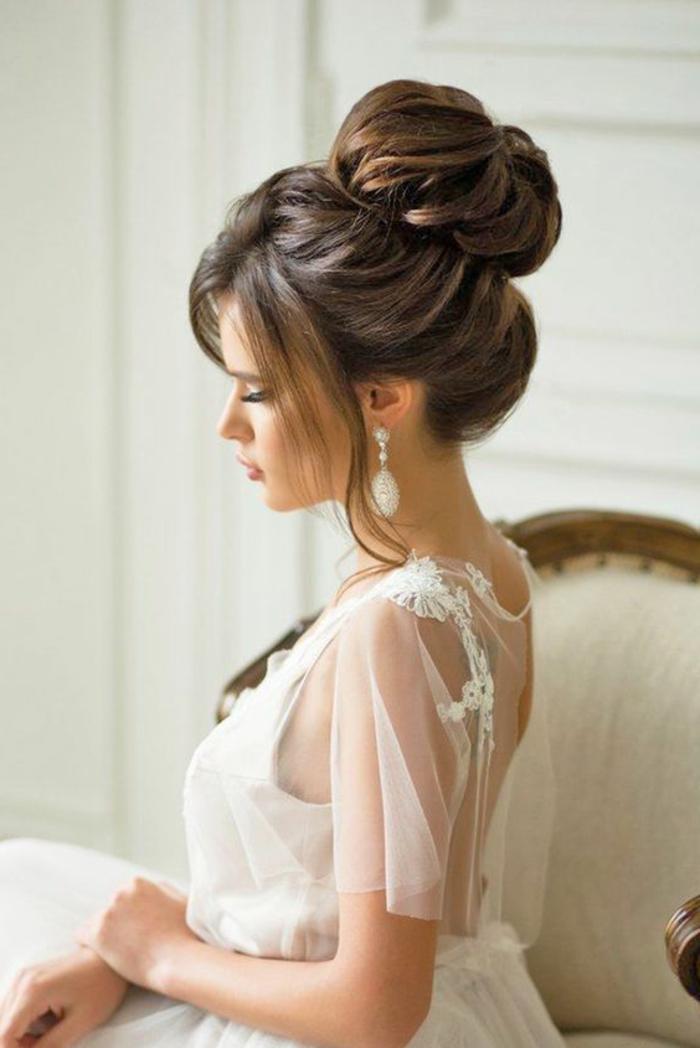 braut mit weißem kleid mit dekorationen und eleganter dut-frisur