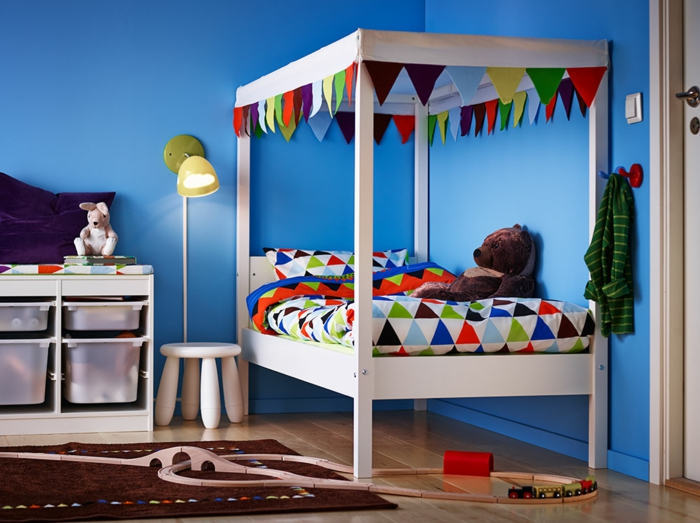 kinderzimmer gestalten blaue wände weißes bett bunte bettdecke brauner teppich ideen deko