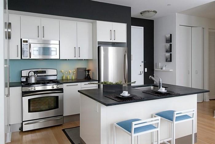 küche-schwarze-wände-parkettboden-kochinsel-blaue-stühle-weiße-küchenschranktüren