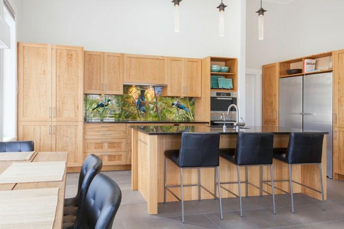 küche mit hölzernen schränken und küchenrückwand mit vögeln