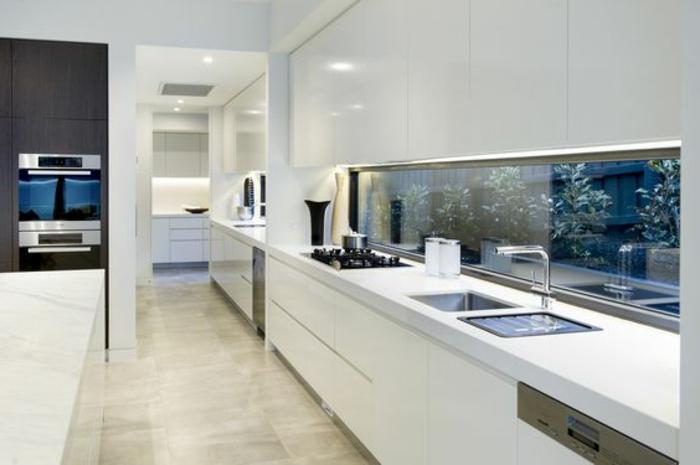 elegante küche in weiß mit glasrückwand mit pflanzen