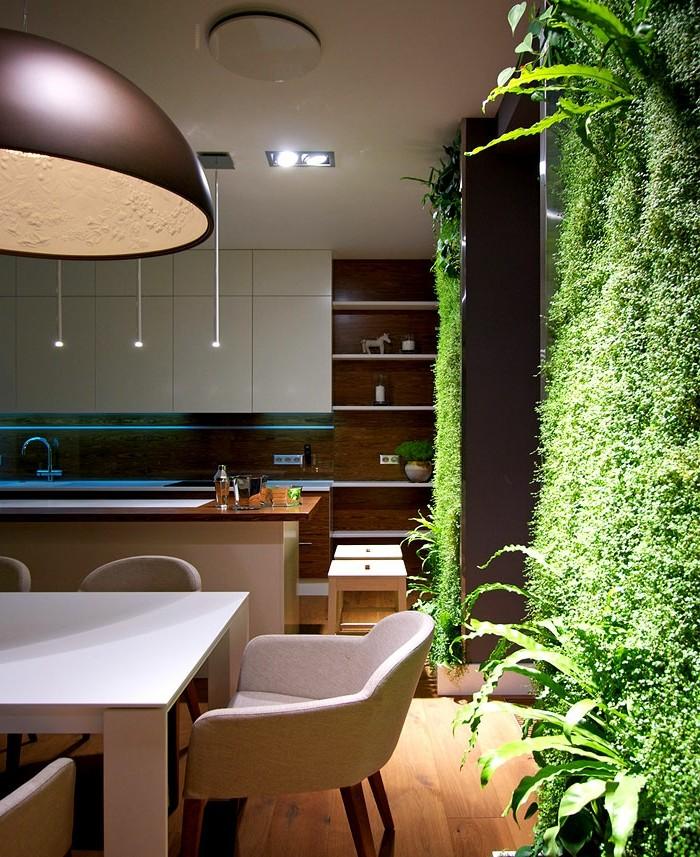 küchenschranktüren-weiß-push-to-open-holzwand-weißer-tisch-sessel-kochinsel-pflanzenwand-indirektes-licht