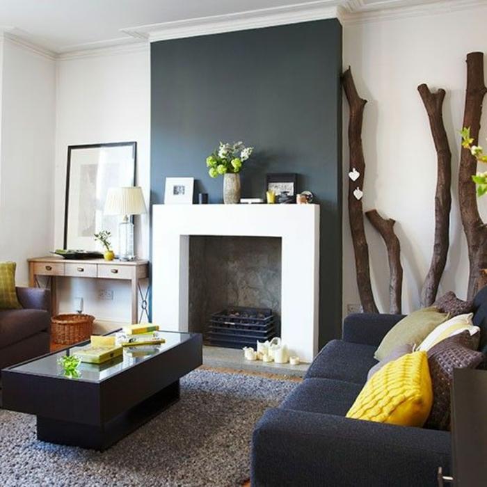 kamin-gemauert-blau-graue-wand-teppich-viereckiger-couchtisch-glas-dunkle-couch-leselampe-holzdeko