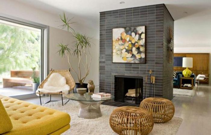 kamin-gemauert-gelbe-couch-holzhocker-flechthocker-flechtstuhl-pelzdecke-runder-glastisch-weißer-teppich