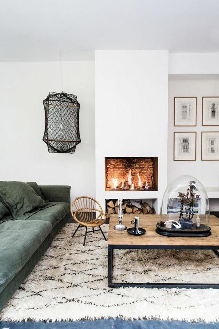 kamin-gemauert-grüne-couch-musterteppich-weiß-schwarz-couchtisch-massivholz-tischdeko-holzstuhl
