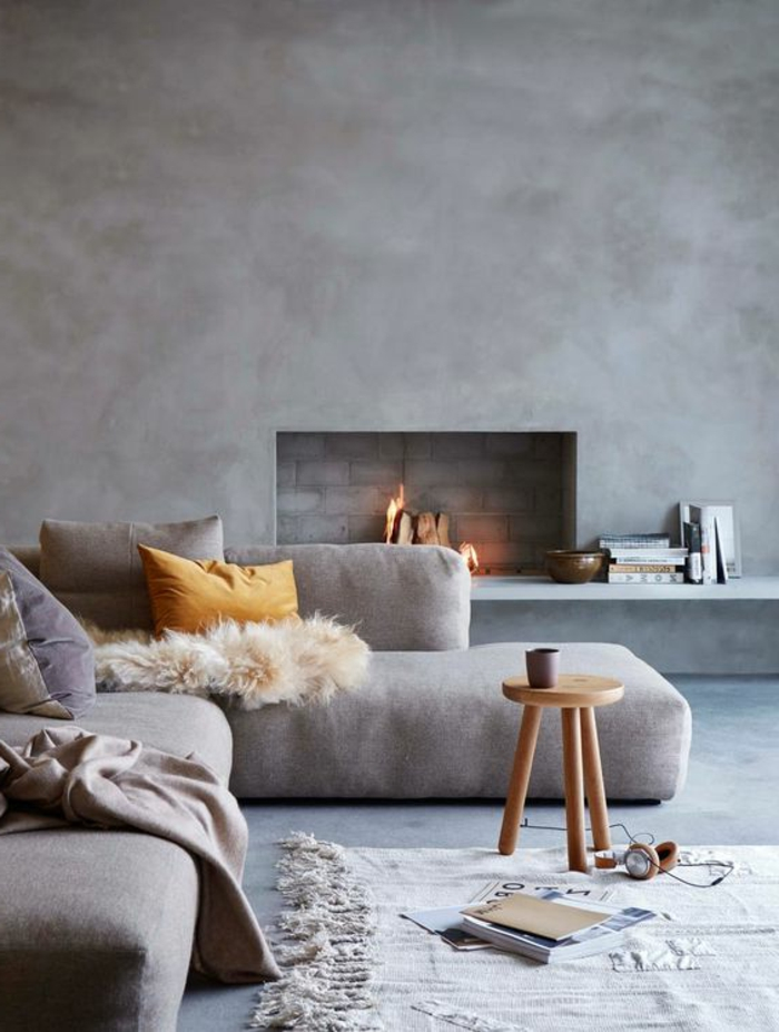 kamin-gemauert-graue-eckcouch-weißer-teppich-holzhocker-kleiner-runder-holztisch-bücher-kaminregal