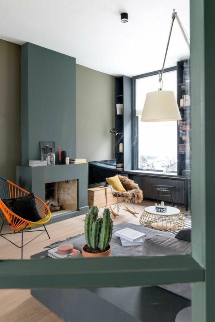 kamin-gemauert-laminat-farbige-wände-flechtstuhl-gelb-orange-schwarze-kisse-schaukelstuhl-kaktus-runder-couchtisch