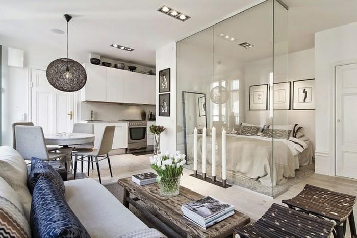 kleine-wohnung-einrichten-doppelbett-glasabtrennung-tisch-massivholz-holzhocker-weiße-couch-blaue-kissen