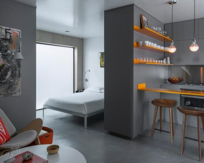 kleine-wohnung-einrichten-grau-gestalten-orange-küchenregale-bar-doppelbett-weißer-rundtisch-indirektes-licht
