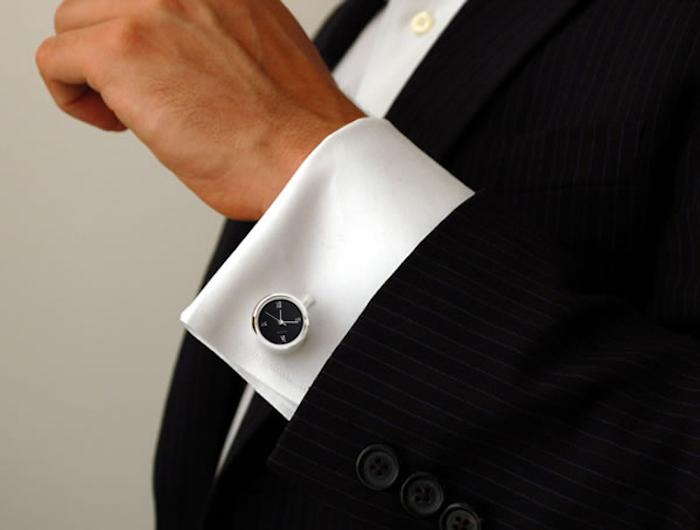 elegant gekleideter Mann mit weißem Hemd, schwarzem Sakko mit weißen Streifen, Manschettenknöpfen
