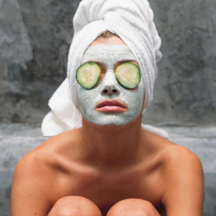 maske diy mitesser maske hausmittel gegen unreine haut maske diy maske gesicht hausmittel gegen entrötungen frau mit gesichtsmaske zwei gurkenscheiben auf den augen kopftuch