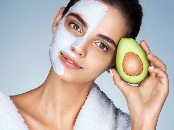 maske selbstgemacht hautmittel gegen unreine haut feuchtigkeitsmasken selber machen anti pickel maske peel of maske mit avocado frau halbes gesicht mit maske hält avocado