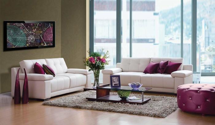 modernes-Wohnzimmer-weißer-Sofa-Bild-lila-Dekokissen-helbrauner-Teppich-großer-Fenster-Kaffeetisch