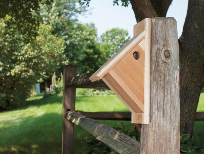 ein Holzhaus für Vögel in dreieckiger Form