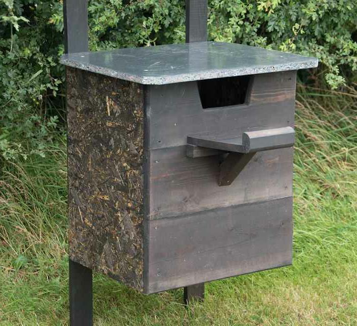 Vogelhaus aus dunklem Holz mit einer Marmorplatte