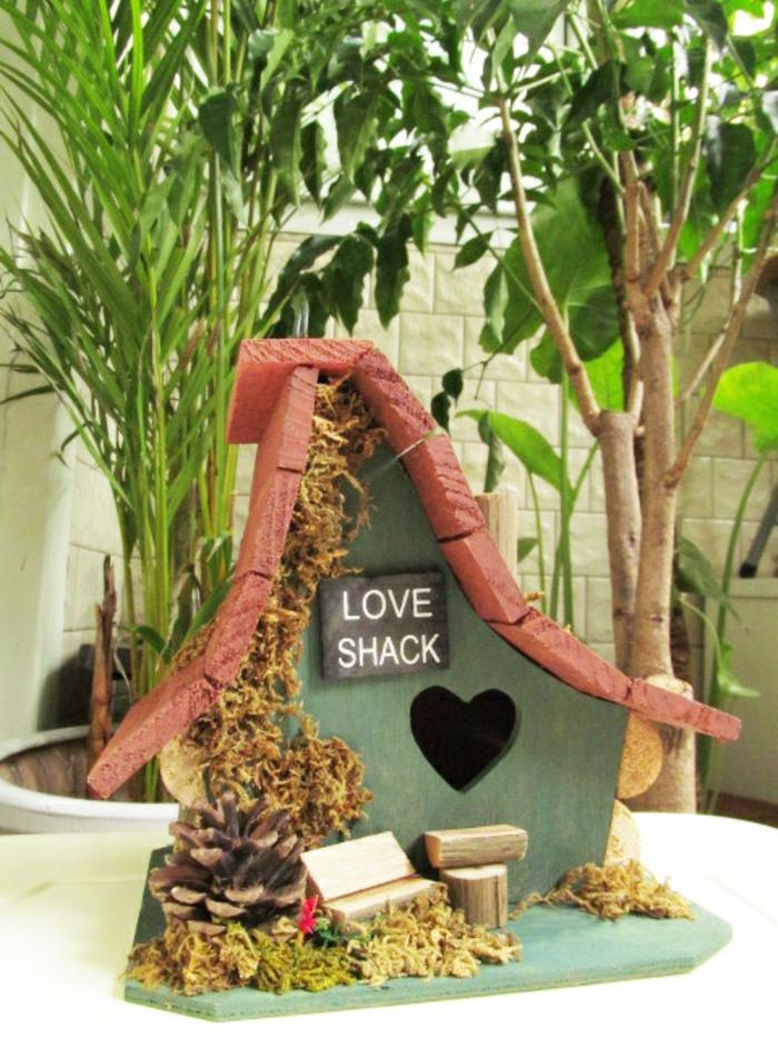 Vogelhaus aus Holz, Zapfen und Gras