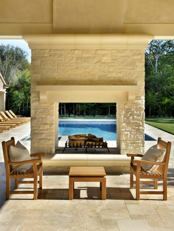 offene-feuerstelle-steinwand-naturstein-massive-gartenmöbel-holzmöbel-schwimmbad-liegestühle