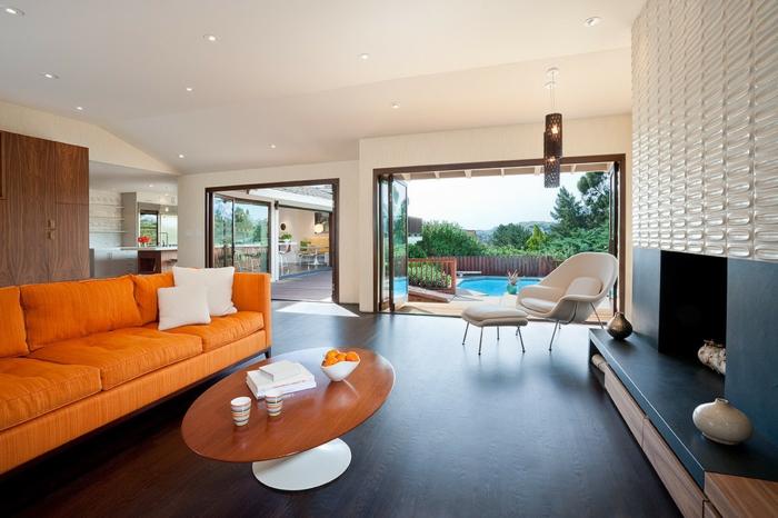 offene-feuerstelle-wandverkleidung-laminat-dunkel-holzverkleidung-orange-couch-ovaler-tisch-schwimmbad-garten