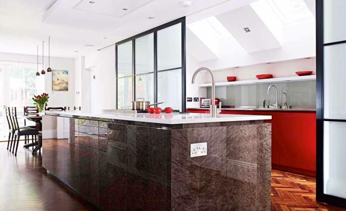 offene-küche-mit-theke-glastrennung-parkettboden-rote-küchenfronten-rote-schüssel-esszimmertisch-blumen